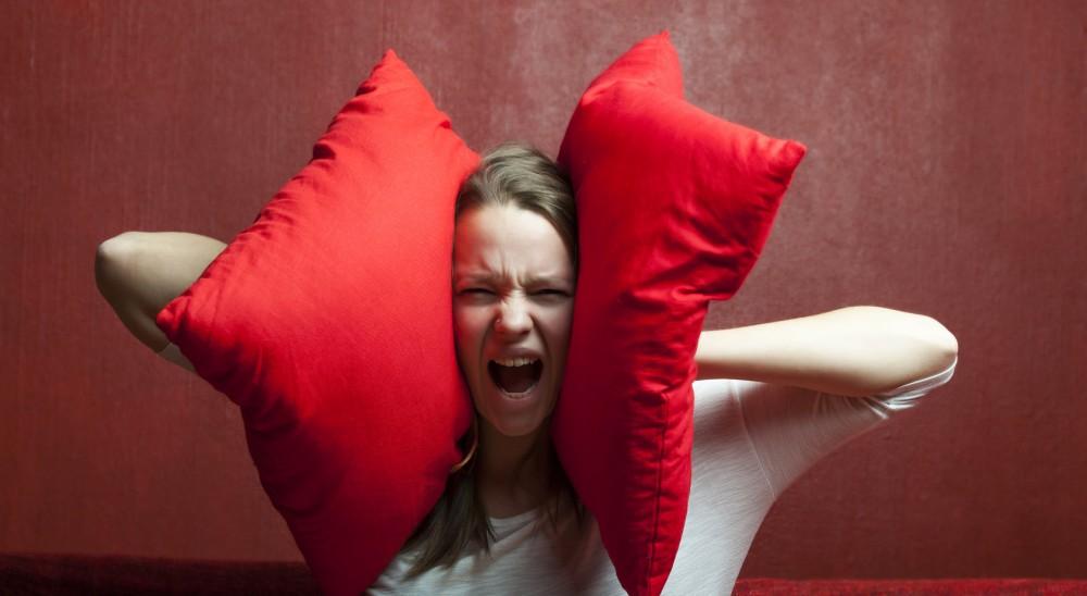 Une jeune femme se protège les oreilles avec des coussins